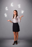 Young lady standing and juggling with currency icons Stock Image