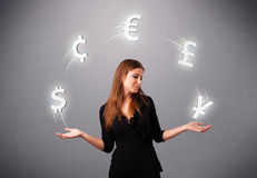 Young lady standing and juggling with currency icons Royalty Free Stock Photography