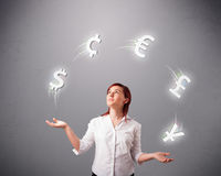 Young lady standing and juggling with currency icons Stock Photos