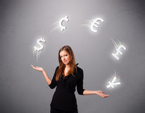 Young lady standing and juggling with currency icons Stock Photography