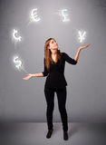 Young lady standing and juggling with currency icons Royalty Free Stock Images