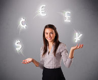 Young lady standing and juggling with currency icons Royalty Free Stock Image