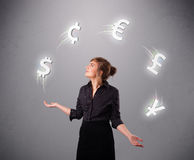 Young lady standing and juggling with currency icons Royalty Free Stock Photo
