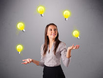 Young lady standing and juggling with light bulbs Stock Photo