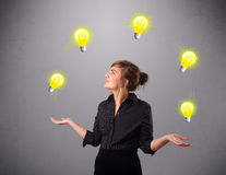 Young lady standing and juggling with light bulbs Royalty Free Stock Photography