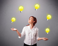 Young lady standing and juggling with light bulbs Royalty Free Stock Image