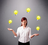 Young lady standing and juggling with light bulbs Royalty Free Stock Photo