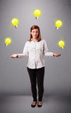 Young lady standing and juggling with light bulbs Stock Photography