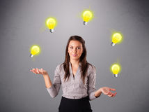 Young lady standing and juggling with light bulbs Stock Image