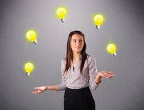 Young lady standing and juggling with light bulbs Royalty Free Stock Photos