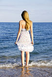 Young lady standing in the sea waves Royalty Free Stock Photo