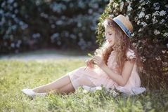 Young lady in a straw hat on a spring lawn among flowering bushes Royalty Free Stock Image
