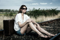 Young lady with suitcase. Young lady sit on the rails with old fashioned suitcase Royalty Free Stock Images