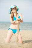 Young lady sunbathing on a beach. Beautiful woman posing at the Stock Photos