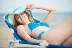 Young lady sunbathing on a beach. Beautiful woman posing at the. Summer sand beach. Outdoor summer portrait of pretty sport style woman in blue bikini. Ocean Stock Images