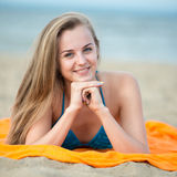 Young lady sunbathing on a beach. Beautiful woman posing at the Royalty Free Stock Images