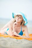 Young lady sunbathing on a beach. Beautiful woman Stock Photos