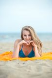 Young lady sunbathing on a beach. Beautiful woman Royalty Free Stock Images