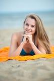 Young lady sunbathing on a beach. Beautiful woman Stock Photo