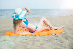 Young lady sunbathing on a beach. Beautiful woman Royalty Free Stock Photos