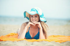 Young lady sunbathing on a beach. Beautiful woman Stock Photo