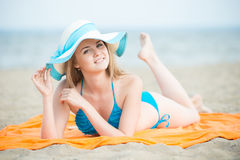 Young lady sunbathing on a beach. Beautiful woman Royalty Free Stock Photography