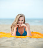 Young lady sunbathing on a beach. Beautiful woman Royalty Free Stock Image