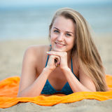 Young lady sunbathing on a beach. Beautiful woman posing at the Stock Image