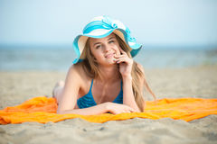 Young lady sunbathing on a beach. Beautiful woman posing at the. Summer sand beach. Outdoor summer portrait of pretty sport style woman in blue bikini. Ocean Royalty Free Stock Images