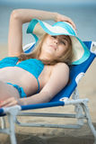 Young lady sunbathing on a beach. Beautiful woman posing at the Stock Photo