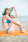 Young lady sunbathing on a beach. Beautiful woman posing at the Royalty Free Stock Photo