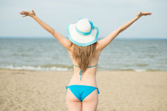 Young lady sunbathing on a beach. Beautiful woman posing at the. Summer sand beach. Outdoor summer portrait of pretty sport style woman in blue bikini. Ocean Stock Image