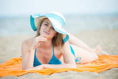 Young lady sunbathing on a beach. Beautiful woman posing at the Stock Photography