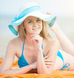 Young lady sunbathing on a beach. Beautiful woman posing at the Royalty Free Stock Photos