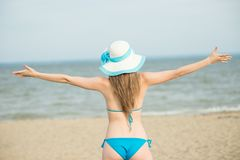 Young lady sunbathing on a beach. Beautiful woman posing at the. Summer sand beach. Outdoor summer portrait of pretty sport style woman in blue bikini. Ocean Stock Photos