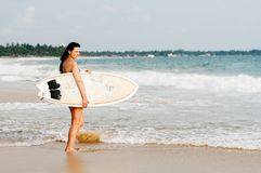Young lady surfer standing on the beach with surf board Royalty Free Stock Images