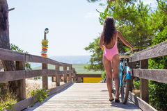 Young lady in swimsuit walking with bicycle on Stock Images