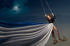 Young lady on a swing above the water royalty free stock photos