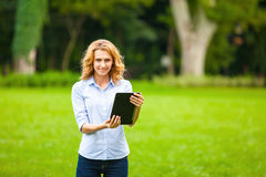 Young lady with tablet in park Stock Image