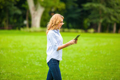 Young lady with tablet in park Stock Photography