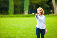 Young lady with tablet in park Royalty Free Stock Photography