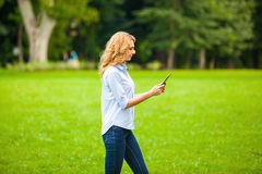 Young lady with tablet in park Royalty Free Stock Photo