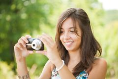 Young lady taking photos outdoors. Beautiful young woman taking photos outdoors in a forest Royalty Free Stock Photography
