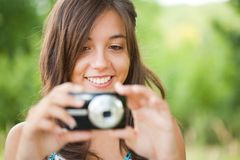 Young lady taking photos outdoors. Beautiful young woman taking photos outdoors in a forest Stock Photography