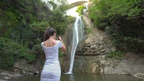 A Young Lady Taking Photos of a Waterfall. stock video