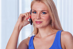 Young lady talking by mobile phone. Portrait of a confident young lady talking by mobile phone with a smile at home Stock Photo