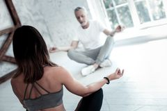 Young lady teaching retired man yoga in class. Relaxed retirement. Selective focus on a turned back brunette women teaching mature men yoga while both sitting in royalty free stock photo