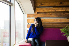 Young lady text sms in phone near window Royalty Free Stock Photography