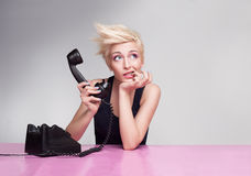 Biting phone. Young lady thinking with her finger in her mouth and holding handset of antique phone Royalty Free Stock Photo