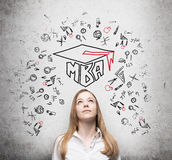 Young lady is thinking about MBA degree. Royalty Free Stock Photography